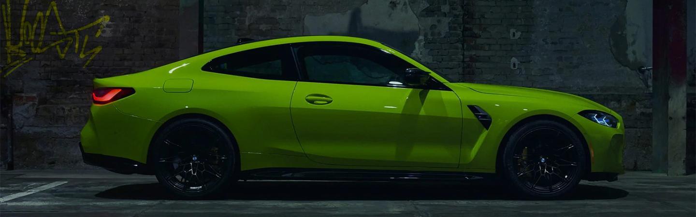 Green 2021 BMW M4 parked in parking garage