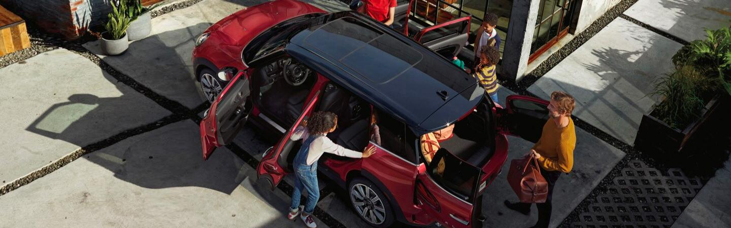Overhead view of a family getting into their red MINI Cooper Clubman