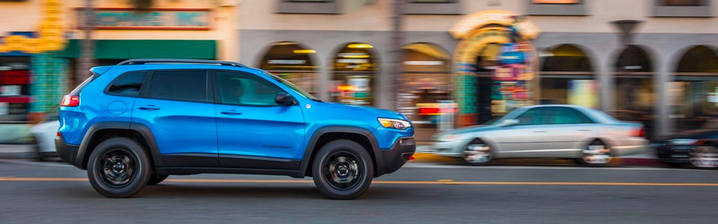 Blue Cherokee in motion in city