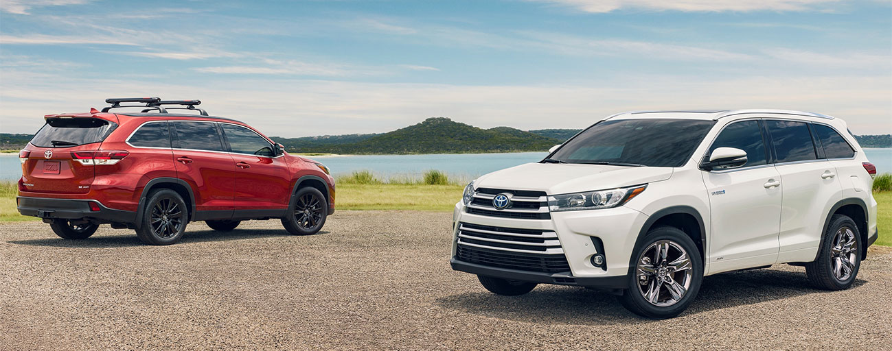Pair of 2019 Toyota Highlander SUVs Exterior - Red and White - Parked by a lake