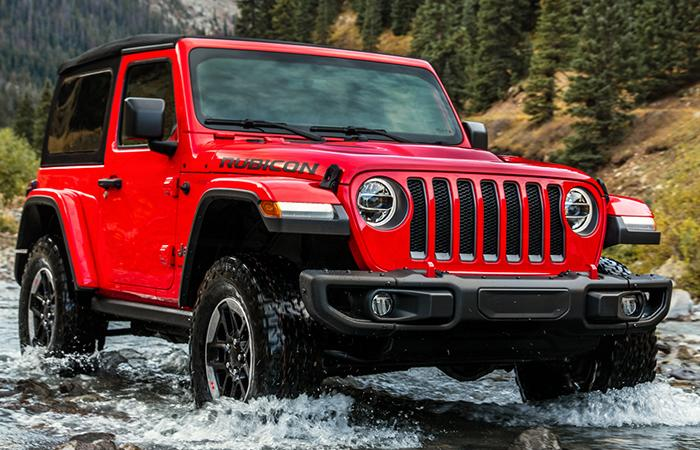 Red 2021 Wrangler driving through a creek