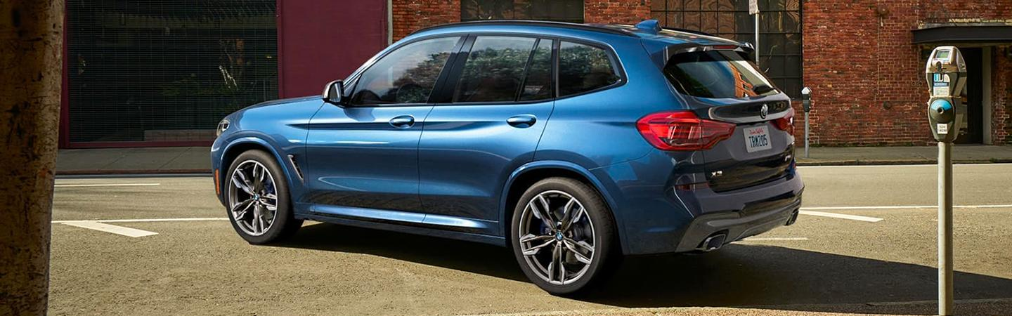 Blue 2020 BMW X3 turning on a road