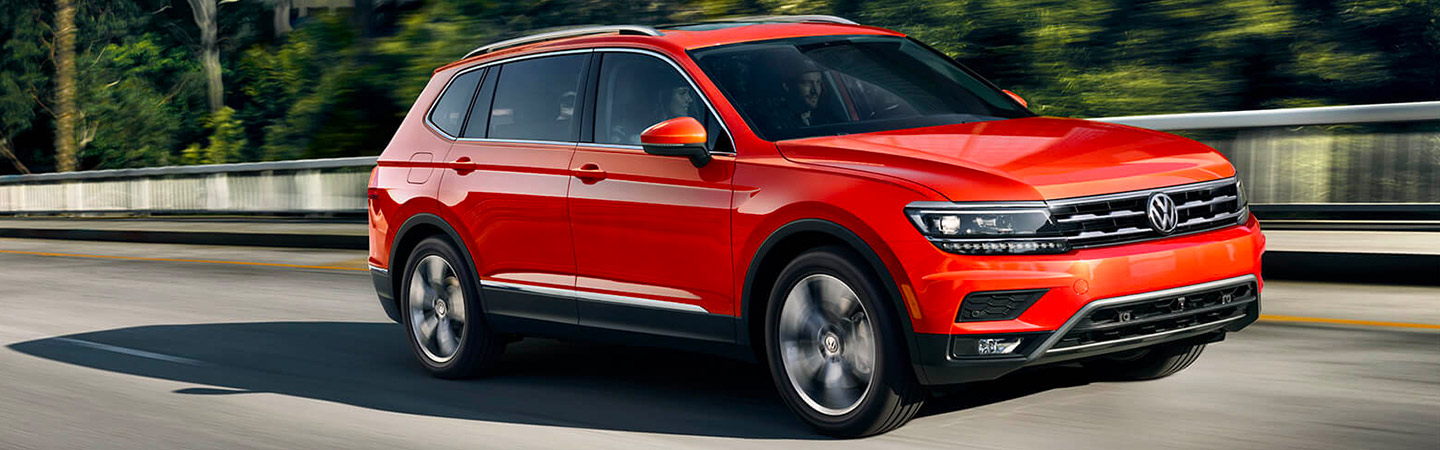 Side profile of a red 2019 Volkswagen Tiguan in motion