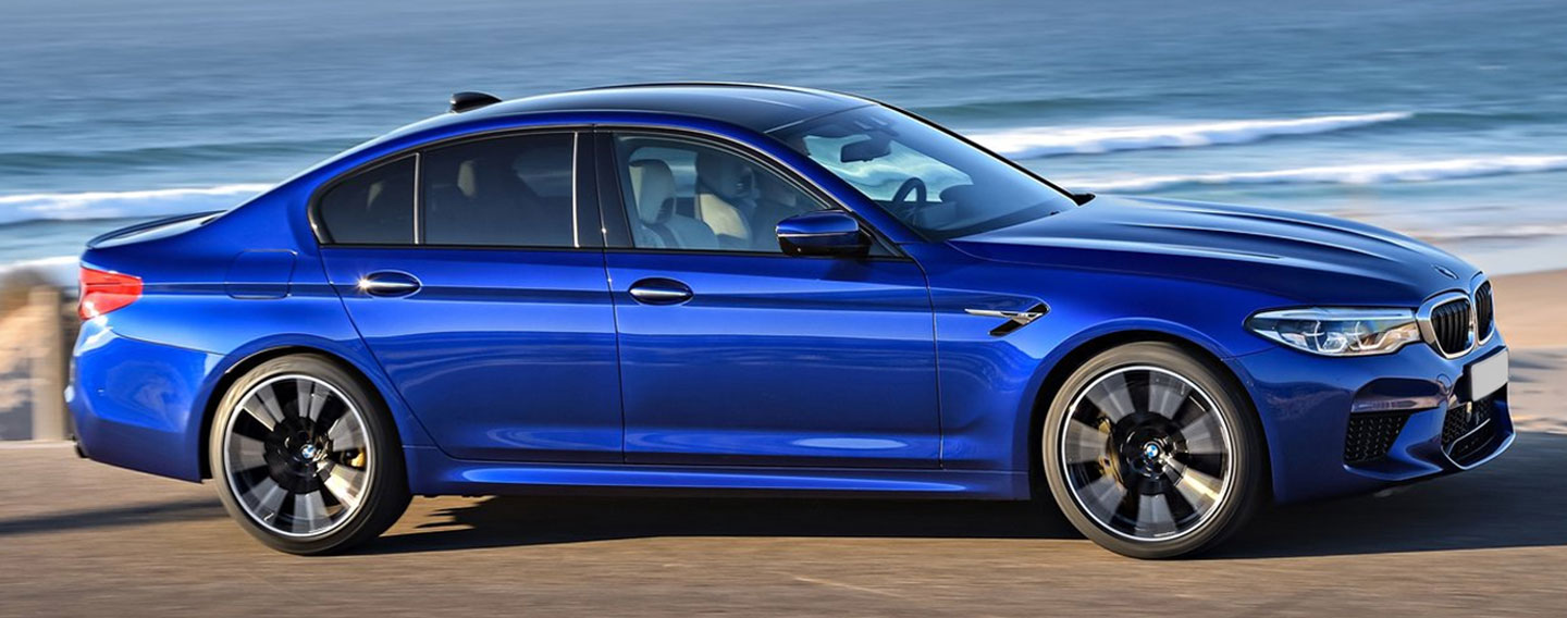Side of BMW M5 driving near the ocean