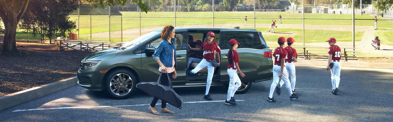 Little league team exiting the green Honda Odyssey