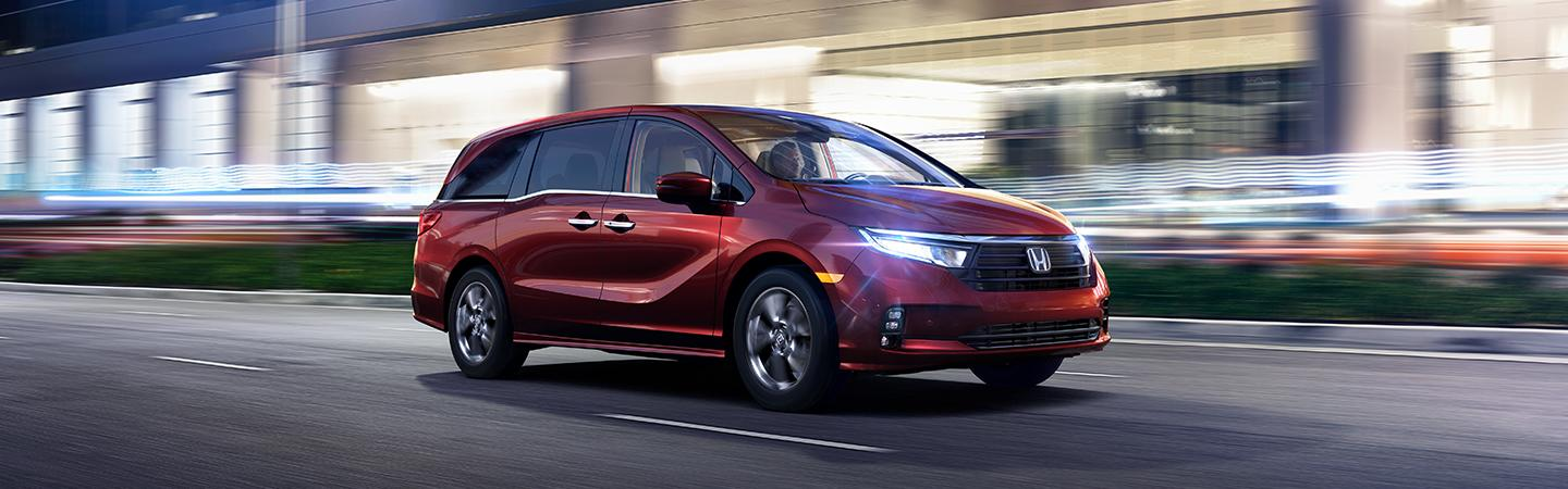 The 2021 red Honda Odyssey in motion