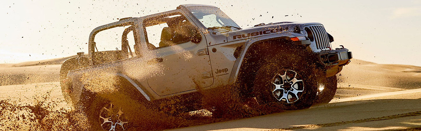 Side view of the 2020 Jeep Wrangler driving up a sand dune