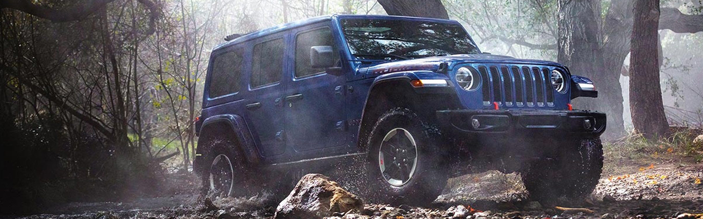 Side view of the 2020 Jeep Wrangler driving through the woods