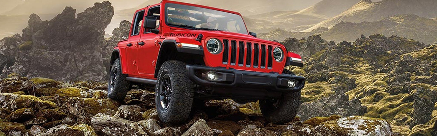 Front view of the 2020 Jeep Wrangler driving up rocks