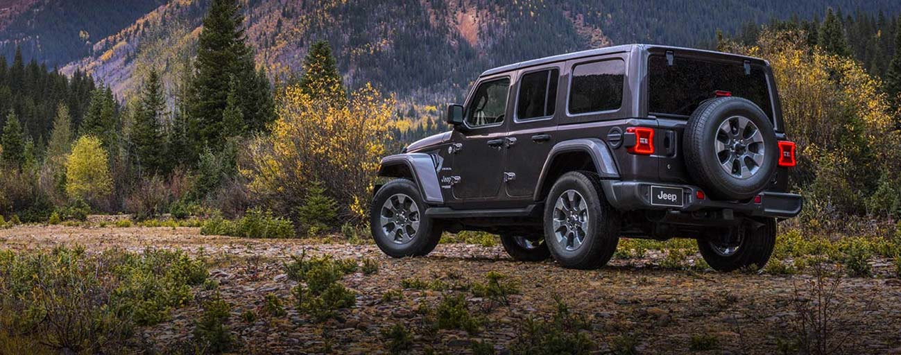 2019 Jeep Wrangler parked offroad at the base of a mountain.
