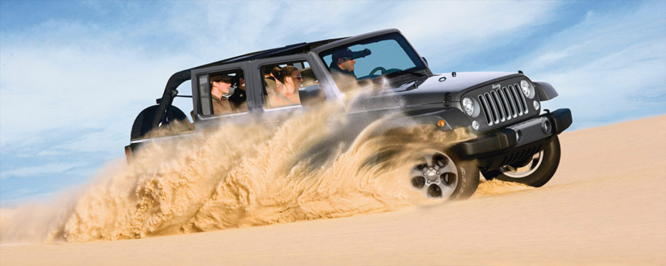 Exterior of the 2018 Jeep Wrangler in sand dunes, available at Naples CDJR in Naples, FL