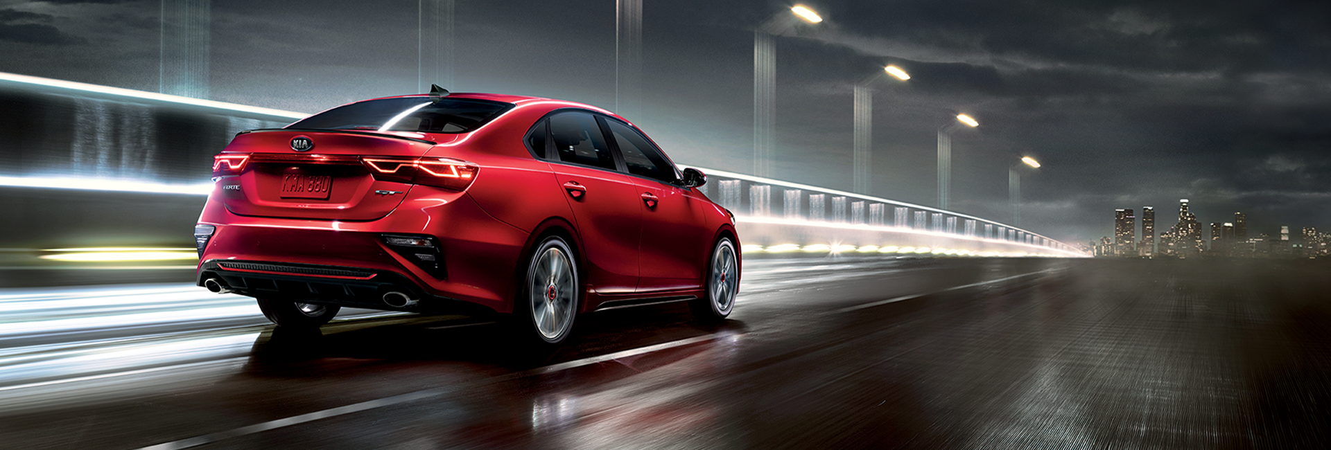 Rear view of a red 2021 Kia Forte in motion