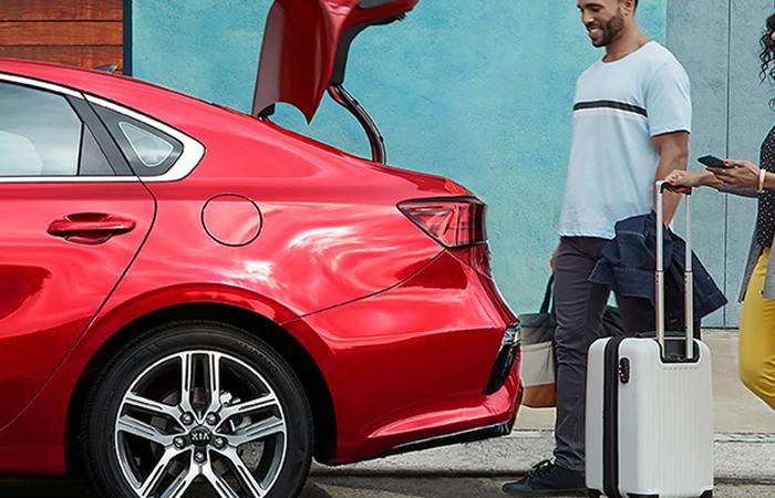 Couple loading luggage into the trunk of a 2021 Kia Forte