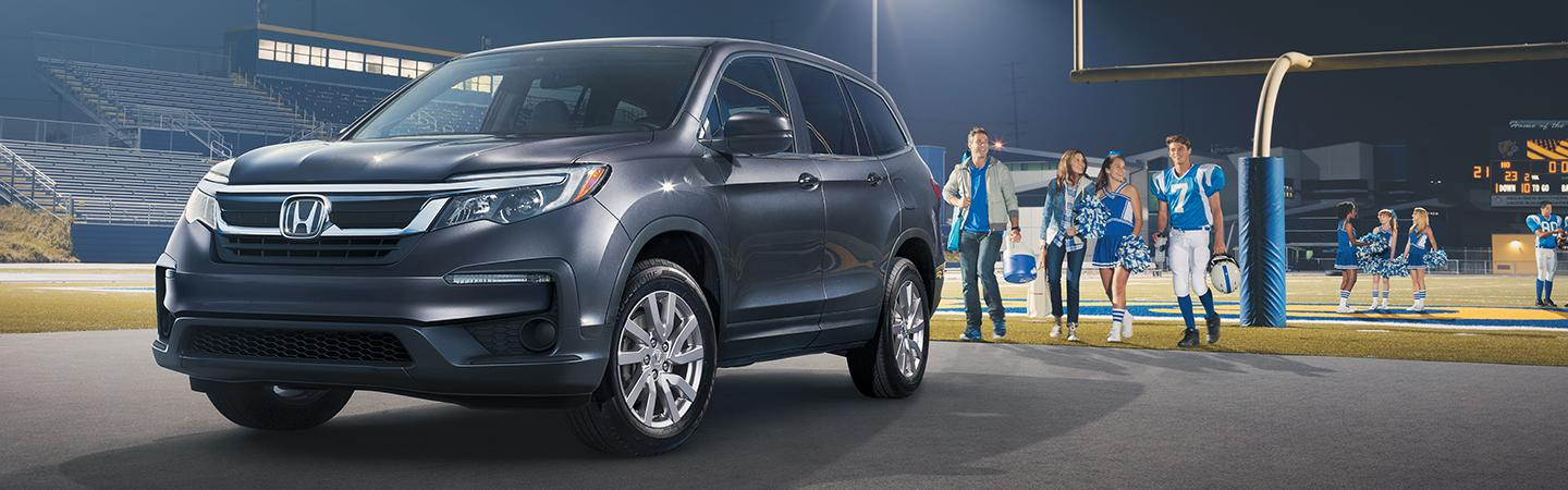 Front view of the 2020 Honda Pilot parked next to a sports field