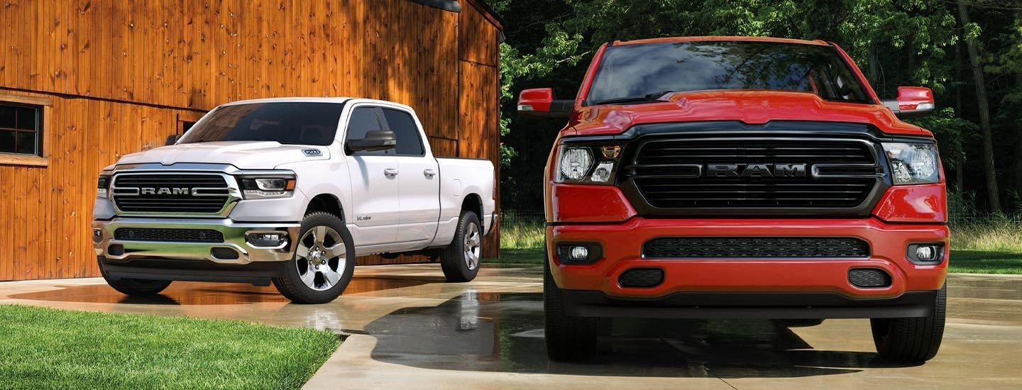 Two RAM 1500 vehicles parked together outside Naples CDJR