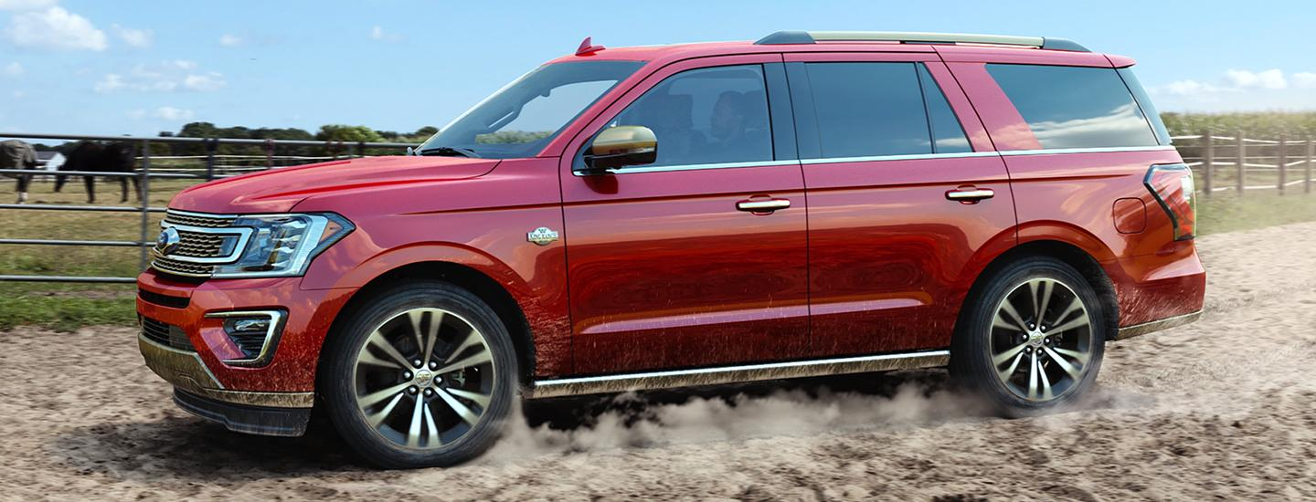 Side view of the 2020 Ford Expedition driving through dirt
